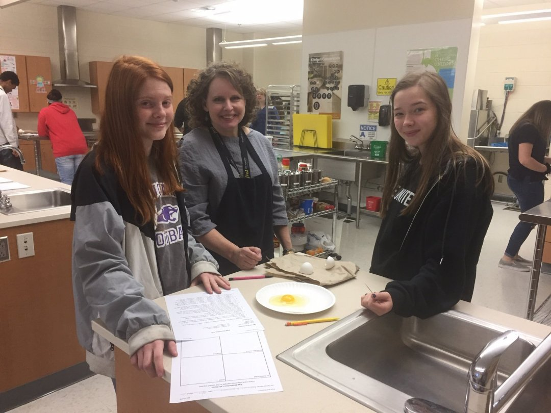 Left to Right, Makayla Smith,10th grade, Mrs. Sandra Hinkle Food and Consumer Sciences Teacher, and Samantha Perdue, 10th grade, discuss the anatomy of protein during egg dissection in Food and Nutrition class