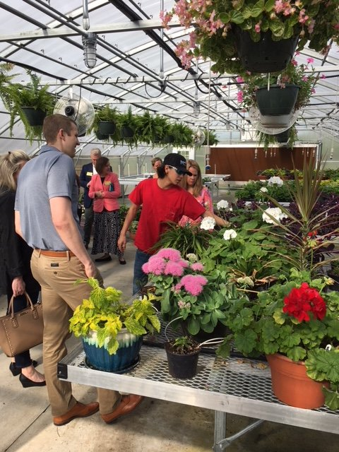 Davie Student Landon Reynolds leads the CTE/STEM Alliance Business Advisory Council members on tour of the horticulture greenhouse at Davie County High School