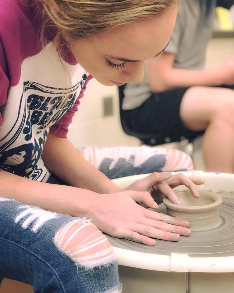 High school student on pottery wheel