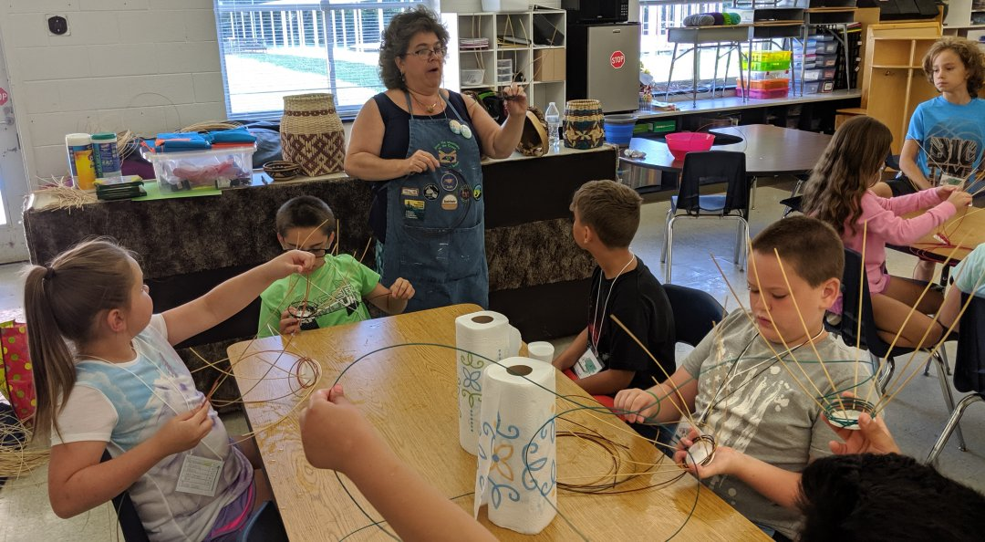 Tami Daniel works with students during an art session