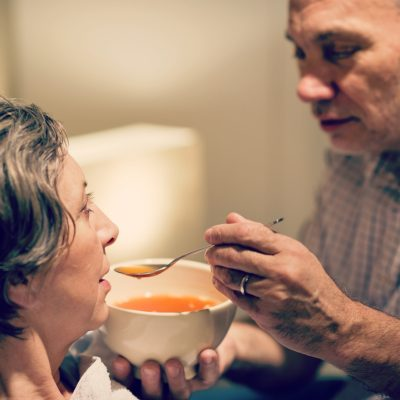 Man cares for his elderly mother feeding her soup