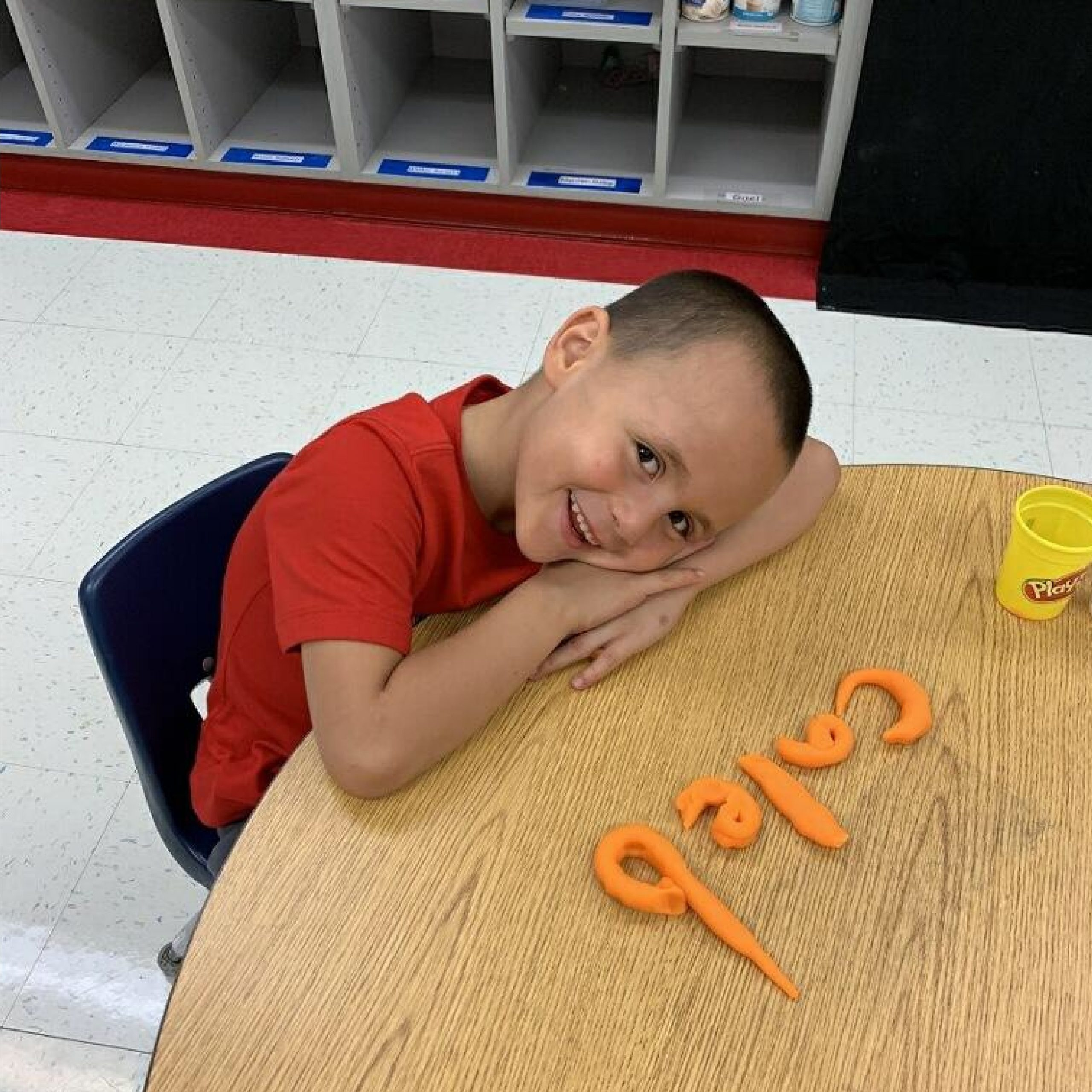 Caleb Fraisier forms his name with playdough during kinder camp at Cooleemee Elementary