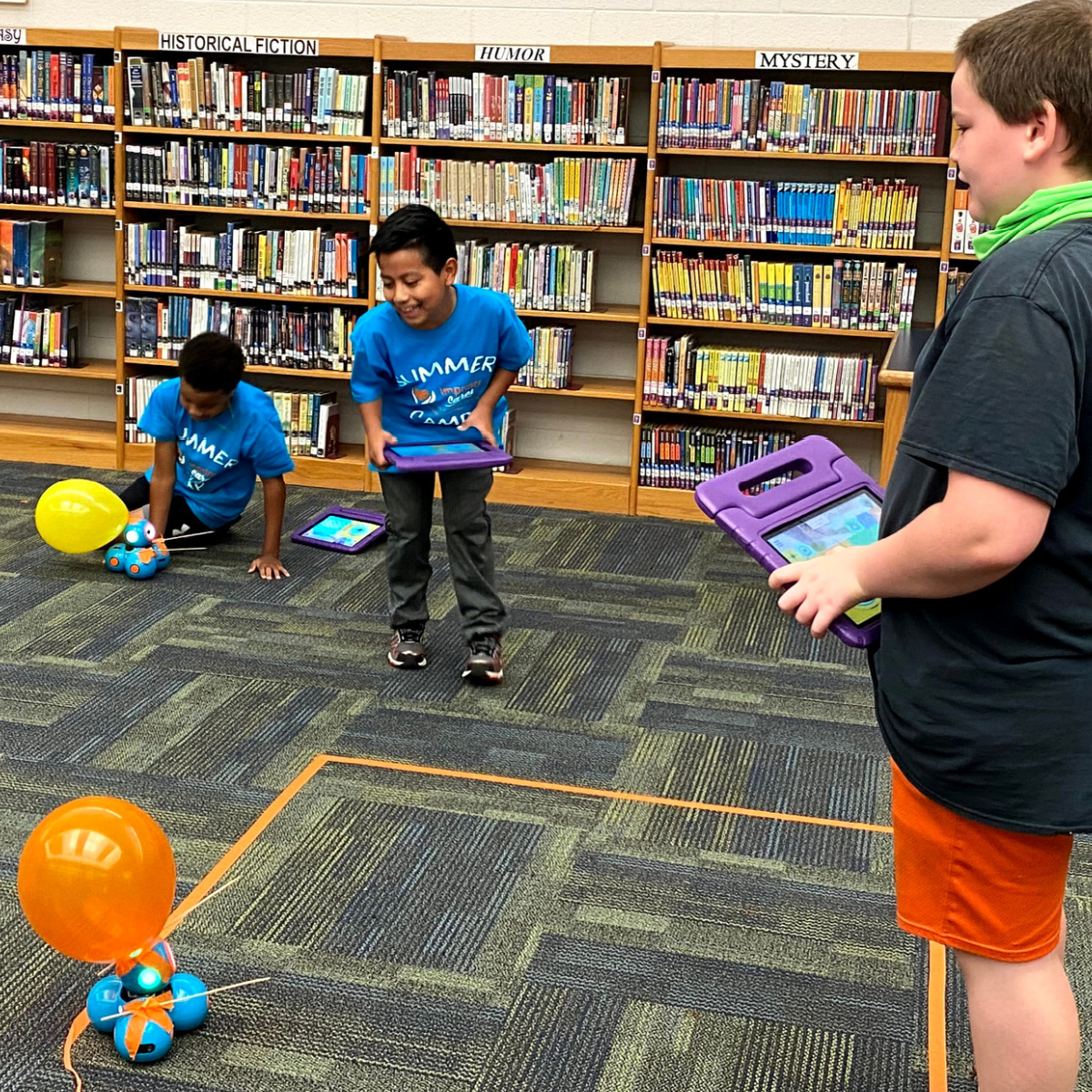 Cayleb Edwards, Brayden Smith and Michael Saunders try to pop each other's balloons with their robotic cars