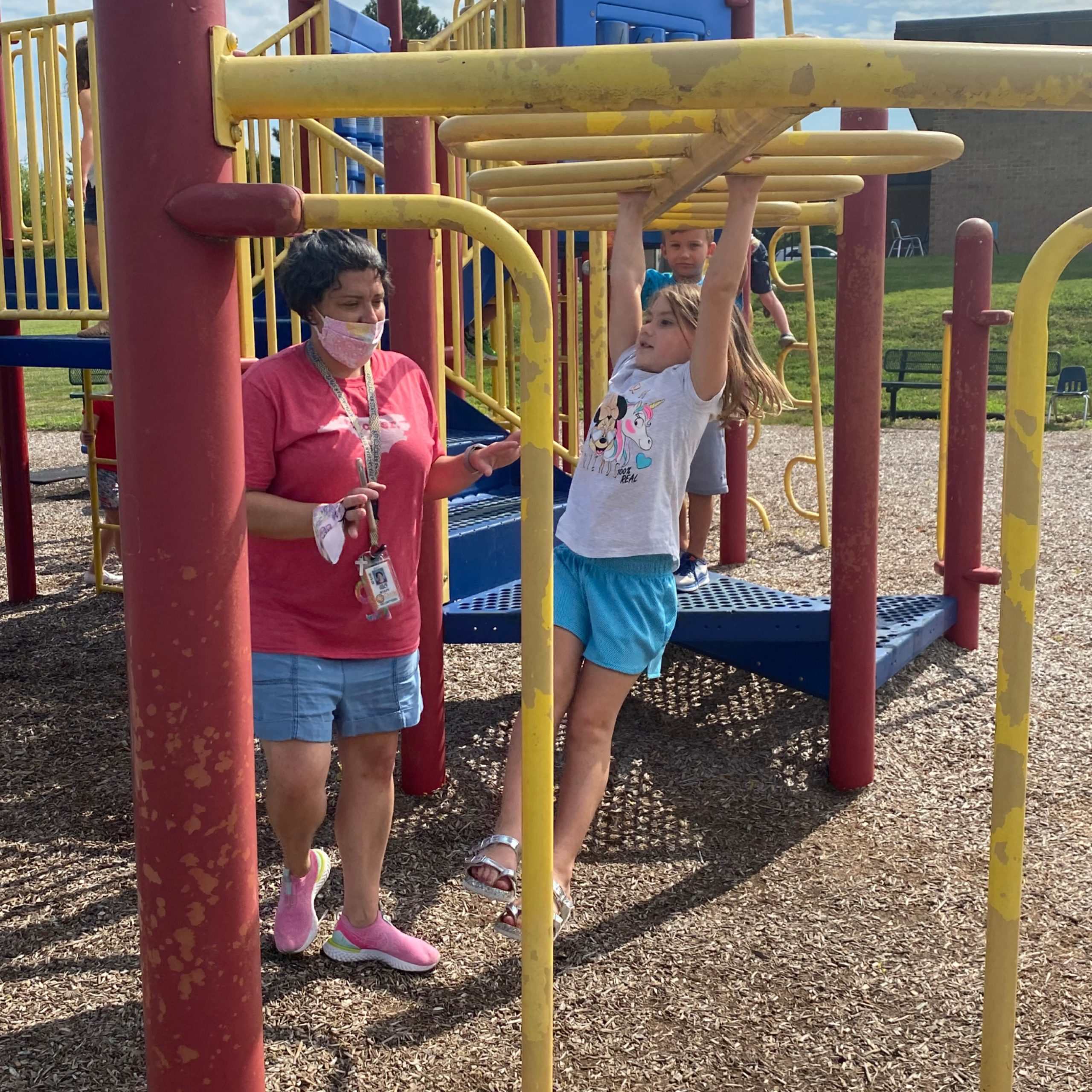 Julie Holt assists Irie Stanbery on the monkey bars during kinder camp at Pinebrook Elementary