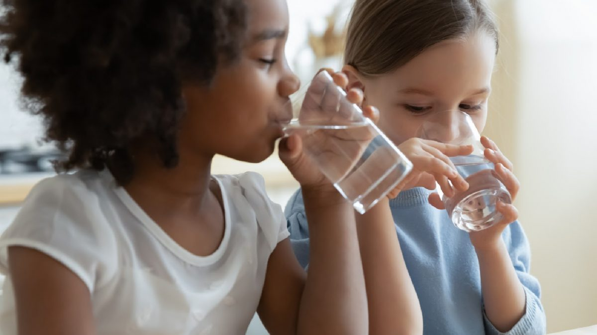 Two girls drink cool clean drinking water from glasses in their homy kitchen.