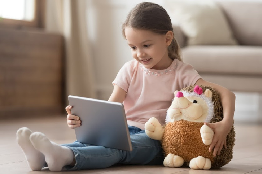 Curious little child girl having fun using digital tablet alone embracing toy sitting on floor, happy preschool smart kid playing with computer looking at screen watching Letterland Videos online at home