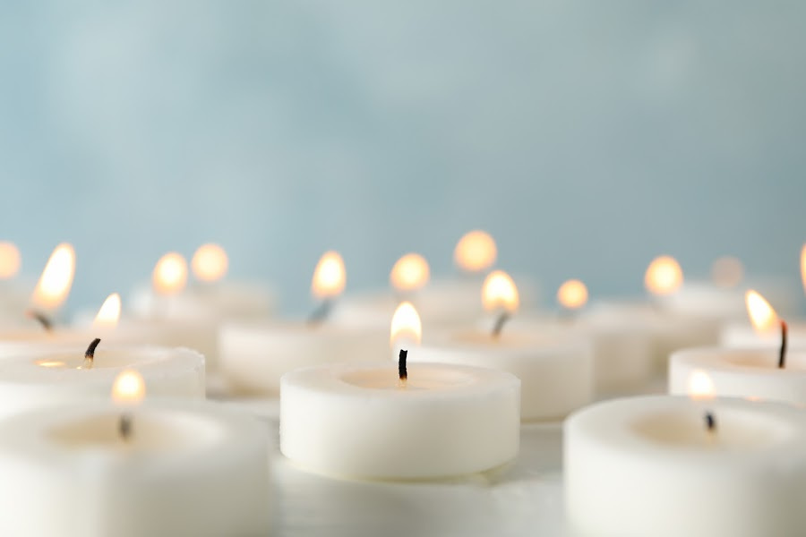 Group of burning candles against blue background, close up