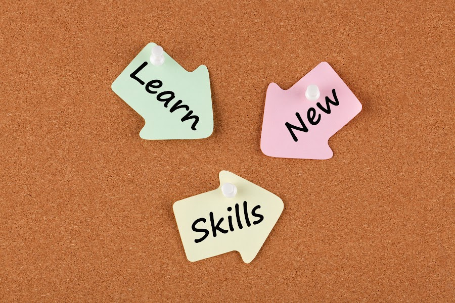 Learn New Skills words on color reminder notes with pin on cork board. Business concept