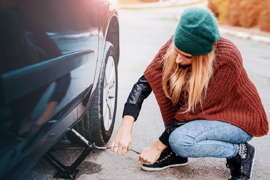 Woman changing wheel at the side of the road after a car breakdown. Cars and transportation