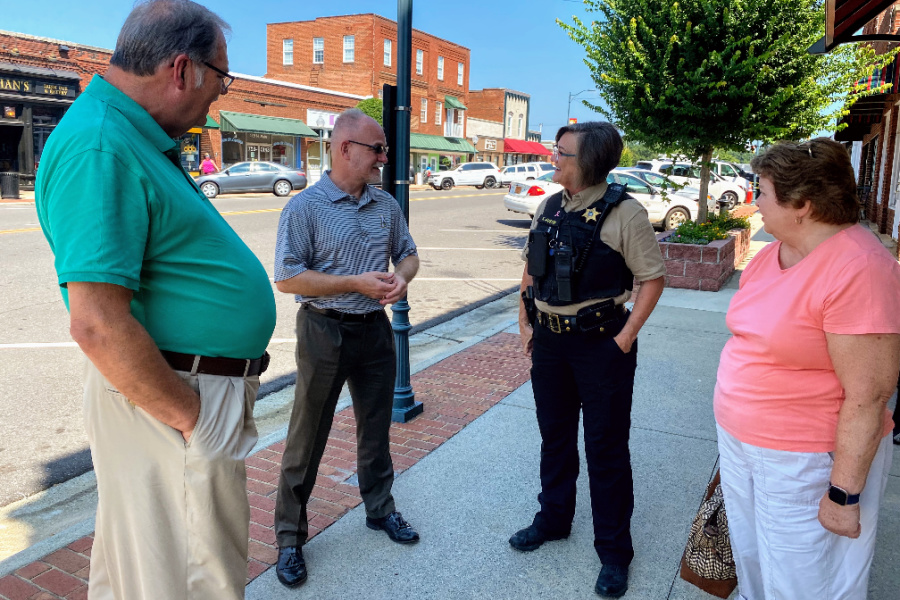(L to R) Bill Campbell, Town Manager Ken Gamble, Officer Karen Austin, and Pat Campbell take a moment to chat on Main Street in Mocksville
